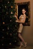 De maniervrouw hing een stuk speelgoed op de Kerstboom royalty-vrije stock fotografie
