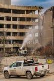De manifestatiebemanning bespuit water om stof in vernieling van het oude Zilveren Dwarsziekenhuis te elimineren Stock Foto