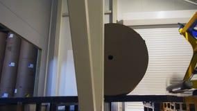 De manipulator duwt verpakkend document broodje aan opslag bij installatie stock videobeelden