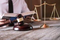 De mannelijke advocaat of de rechter die met Wetsboeken werken, hamer en saldo, meldt het geval over lijst in bureau, Wets en rec stock foto's