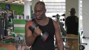 De mannelijke Afro-Amerikaanse atleet doet de krullen van bicepsendomoren terwijl status in gymnastiek stock video