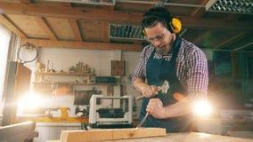De mannelijke arbeider breekt hout met instrumenten af stock videobeelden
