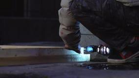 De mannelijke arbeider dient de grijze elektronische schroevedraaier van het jasjegebruik in om planken te verbinden stock video