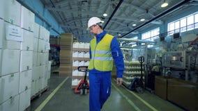 De mannelijke arbeider draagt dozen met plastic schepen stock video