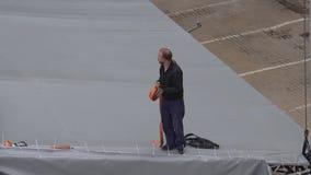 De mannelijke arbeider met lang blondehaar bevindt zich op grijze koepel en houdt oranje lint stock video