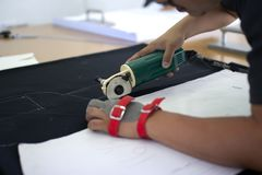 De mannelijke arbeider op een het naaien vervaardiging gebruikt elektrische scherpe stoffenmachine met kettingshandschoen stock foto
