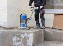de mannelijke arbeiderswerken met de diamant malende machine, die de portiek voor het bureaugebouw oppoetsen de cementvloer en me Royalty-vrije Stock Foto