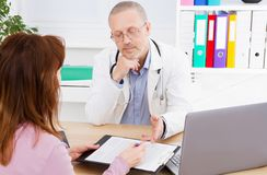 De mannelijke arts bespreekt contract met zijn patiënt in medisch bureau stock foto