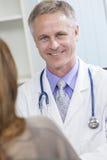 De mannelijke Arts die van het Ziekenhuis aan Vrouwelijke Patiënt spreken Stock Foto's
