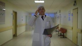 De mannelijke arts gekleed in laboratoriumlaag loopt door de gang van de afdeling en het examinating röntgenogram van een patiënt stock video