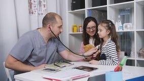 De mannelijke arts in het bureau neemt patiënten De huisarts onderzoekt een klein meisje dat mamma kwam voor een bezoek is E stock videobeelden