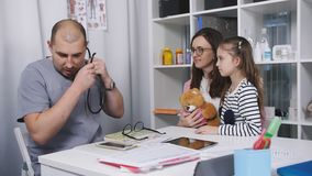 De mannelijke arts in het bureau neemt patiënten De huisarts onderzoekt een klein meisje dat mamma kwam voor een bezoek is E stock video