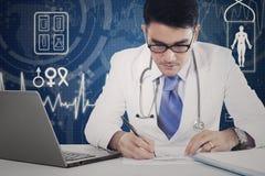 De mannelijke arts maakt medisch recept stock foto's