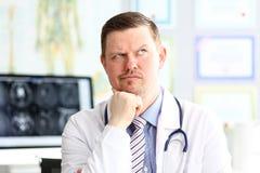 De mannelijke arts met vreemde gelaatsuitdrukking zit in zijn bureau stock foto's