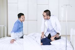 De mannelijke arts onderzoekt een kleine jongen in het ziekenhuis royalty-vrije stock afbeeldingen