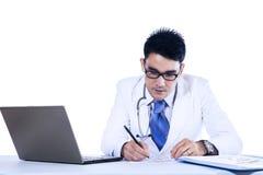 De mannelijke arts schrijft medische rapporten royalty-vrije stock fotografie