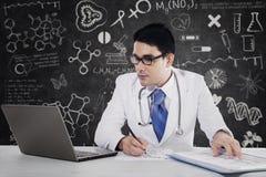 De mannelijke arts schrijft medische rapporten royalty-vrije stock afbeelding