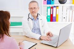 De mannelijke arts spreekt aan vrouwelijke patiënt in het ziekenhuisbureau Gezondheidszorg en de Medische Dienst Het helpen van m stock foto's