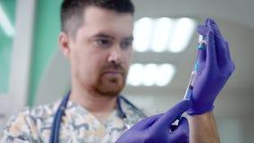 De mannelijke arts vult een spuit door drug vanaf klein glasflesje, voorbereidingen treffend om een injectie in een kliniek te ge stock footage