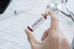 De mannelijke artsenhand houdt drug voor Bloedarmoedeziekte stock afbeelding