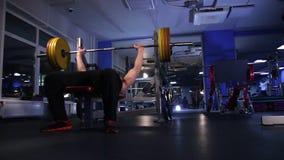 De mannelijke atleet voert de bankpers uit van 140kg barbell Donkerblauwe achtergrond De lengte van de glijdende bewegingsnok stock videobeelden