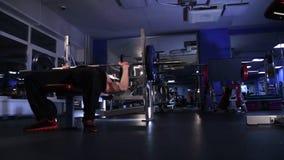 De mannelijke atleet voert de bankpers uit van 80kg barbell De lengte van de glijdende bewegingsnok stock video