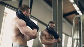 De mannelijke atleet zet op t-shirt die in gymnastiek zich binnen bevinden stock footage