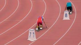 De mannelijke atleten beginnen bij een afstand van 400 meters in stadion stock videobeelden