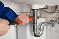 De mannelijke Badkamers van Loodgieterrepairing sink in stock afbeeldingen