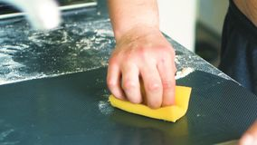De mannelijke bakker maakt keukenlijst van bloem na het koken schoon stock videobeelden
