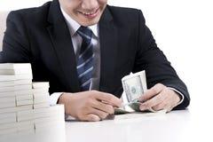 De mannelijke bankier telt bankbiljetten op witte achtergrond Stock Afbeelding