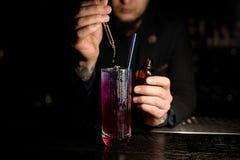 De mannelijke Barman giet alcoholcocktail met druppelbuisje stock foto's