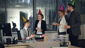 De mannelijke beambte werkt aan computer wanneer zijn medewerkers verjaardagscake en gift brengen en hem gelukwensen stock videobeelden