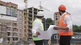 De mannelijke bespreking van de bouwingenieur met architect bij bouwwerf of bouwterrein van highrise de bouw zij stock footage