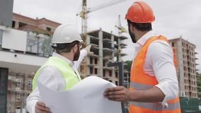De mannelijke bespreking van de bouwingenieur met architect bij bouwwerf of bouwterrein van highrise de bouw zij stock videobeelden