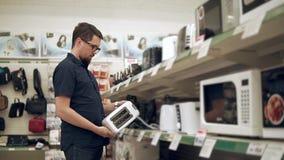 De mannelijke bezoeker neemt in hand tentoonstellingssteekproef van broodrooster in hardwarewinkel stock videobeelden