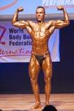 De mannelijke bodybuilder buigt zijn spieren en toont zijn beste lichaamsbouw Stock Fotografie