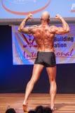 De mannelijke bodybuilder toont zijn beste bij kampioenschap op stadium Stock Afbeelding