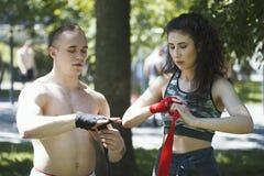 De mannelijke bokser verpakt zijn handen de jonge vrouw hem, training in het park helpt Royalty-vrije Stock Fotografie