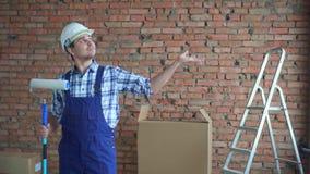 De mannelijke bouwer in een witte helm en eenvormig, toont zijn hand aan copyice stock footage