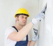 De mannelijke bouwer herstelt muur Stock Foto