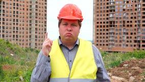 De mannelijke de de bouwersvoorman, arbeider of architect op bouwbouwterrein keuren het golven van zijn vinger niet goed stock video