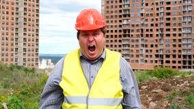 De mannelijke de de bouwersvoorman, arbeider of architect op bouwbouwterrein schreeuwen en kijken aan camera stock videobeelden