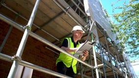 De mannelijke bouwvakker van de bouwersvoorman op bouwterrein die een bouwvakker dragen die op klembord schrijven stock videobeelden