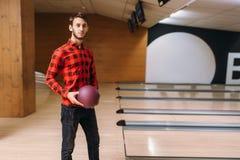 De mannelijke bowlingspeler status op steeg en houdt bal royalty-vrije stock foto's