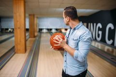 De mannelijke bowlingspeler status op steeg en stelt met bal stock fotografie