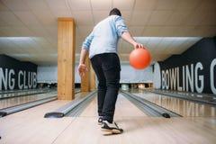 De mannelijke bowlingspeler status op steeg en stelt met bal royalty-vrije stock foto's