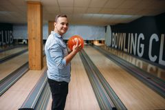 De mannelijke bowlingspeler status op steeg en stelt met bal stock afbeelding