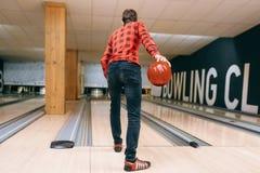 De mannelijke bowlingspeler werpt bal op steeg, achtermening stock afbeeldingen