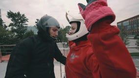 De mannelijke bus instrueert een skydivermeisje alvorens in windtunnel te vliegen stock videobeelden